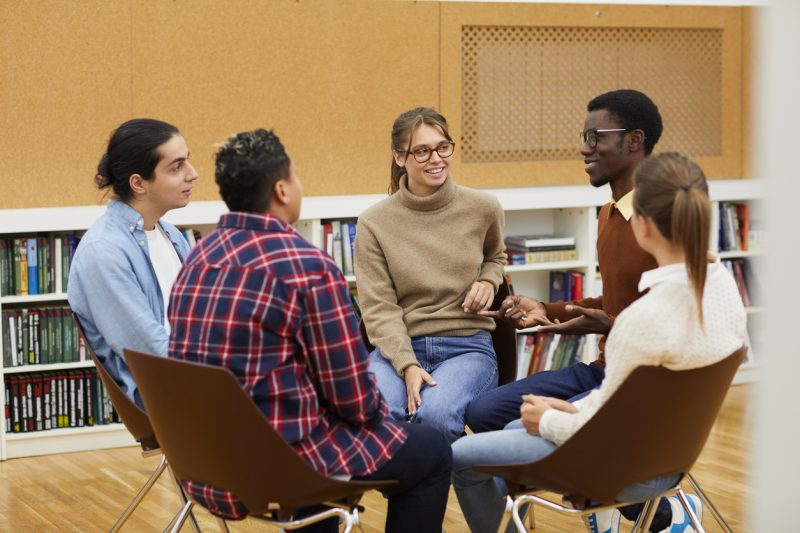 Multi-ethnic group of young people sitting in circle and sharing ideas during class in college, copy space